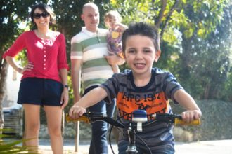 A young boy rides his bike toward the camera while his family smiles in the background