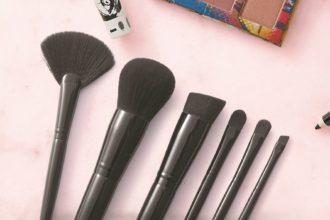 Un conjunto de las seis nuevas brochas de maquillaje Artistry se encuentran sobre un fondo rosa. Se pueden ver sombras de ojos, rímel y delineador de ojos Artistry en los bordes del marco.