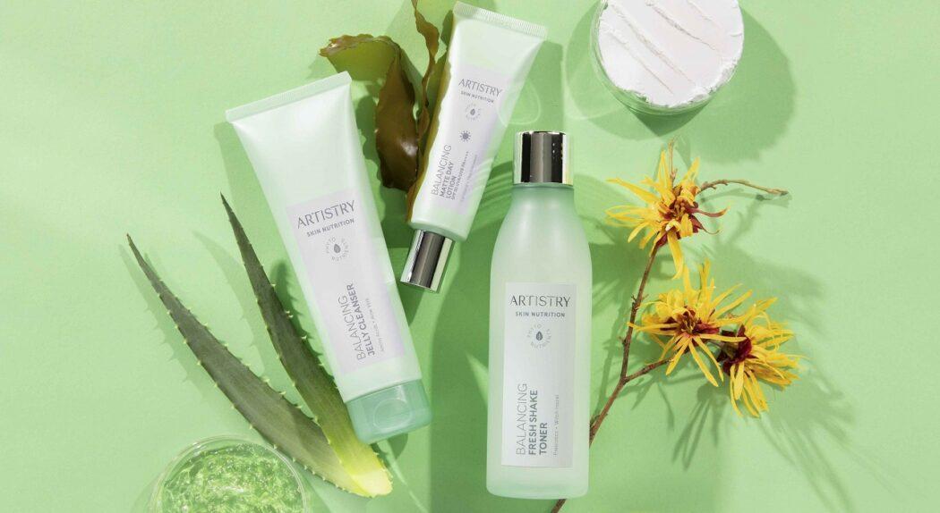 Una colección de productos equilibrantes Artistry Skin Nutrition que yacen sobre una encimera junto a algunos de sus ingredientes.