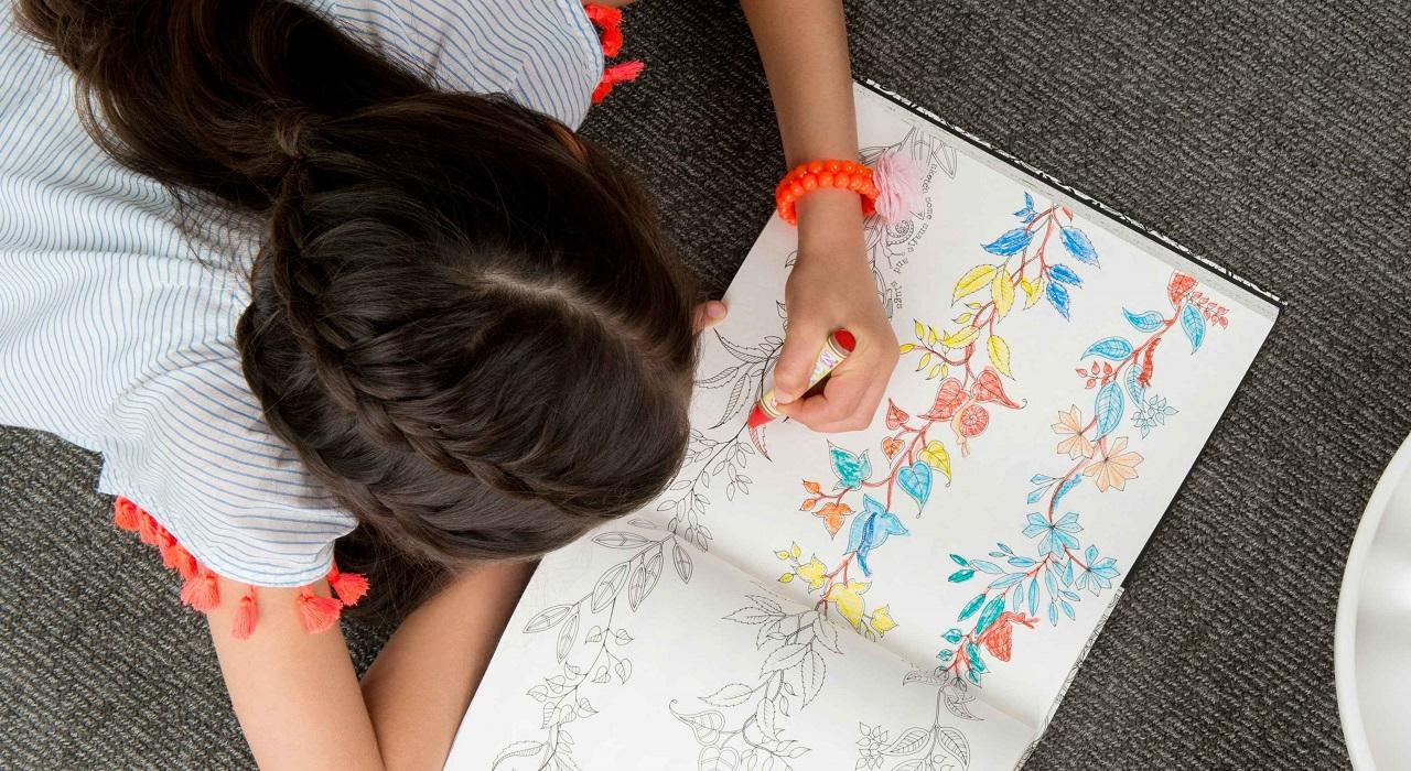 Una vista aérea de un joven coloreando un libro para colorear en el suelo.