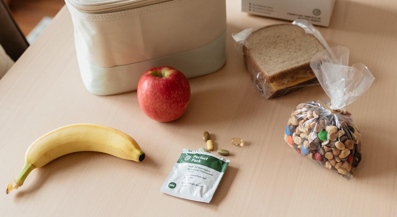 El contenido de un almuerzo saludable está en una mesa listo para empacar, incluido un paquete abierto de Nutrilite Perfect Pack con las tabletas derramadas.