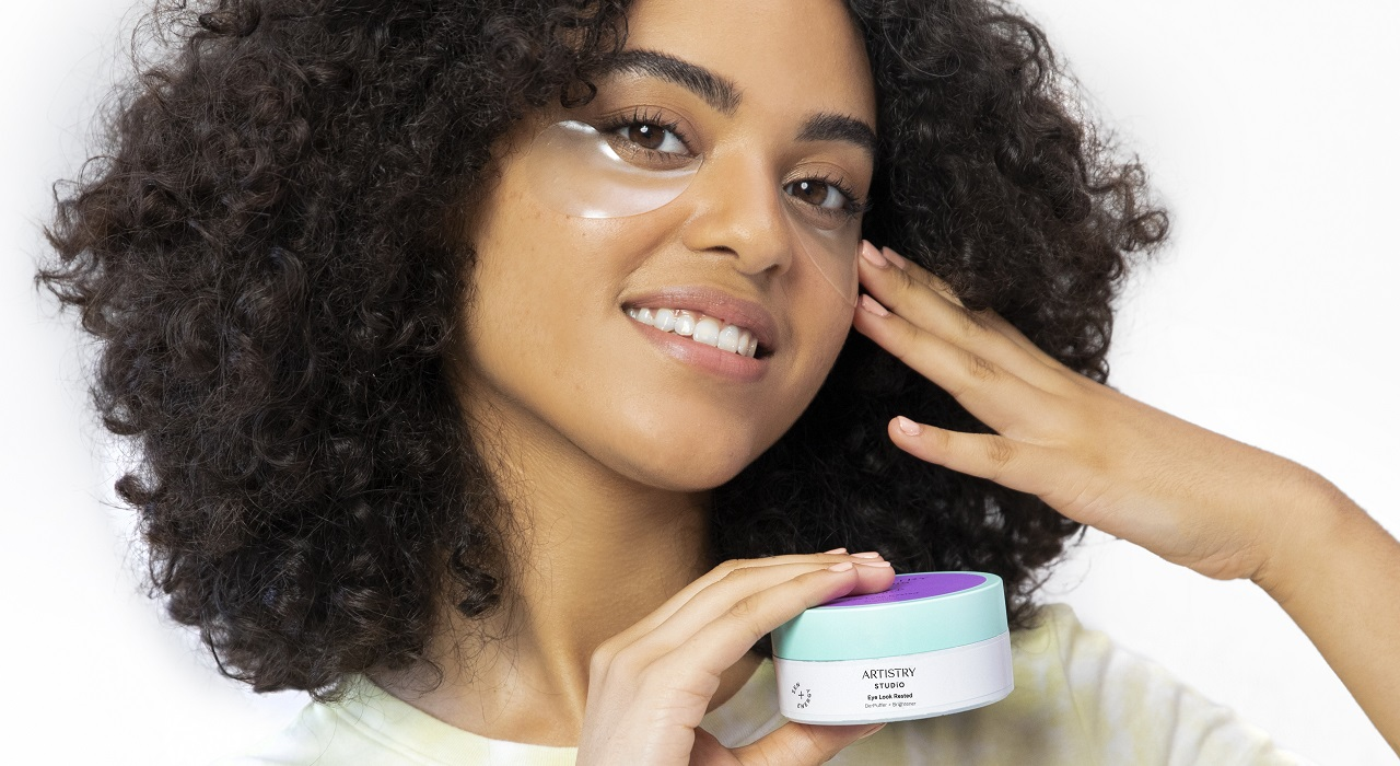 A person with thick, dark curly hair demonstrates the Artistry Studio Eye Look Rested De-Puffer + Brightener patch while holding a jar of them.