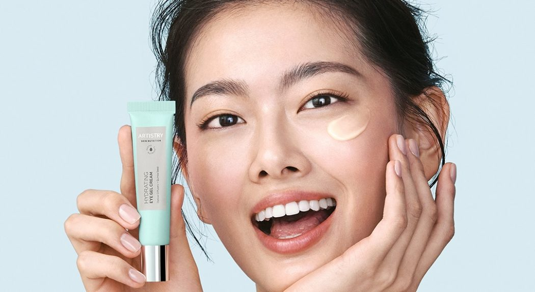 A person holds up a tube of Artistry Skin Nutrition™ Hydrating Eye Gel Cream near the right side of their face. They have already applied some of the product under their left eye.