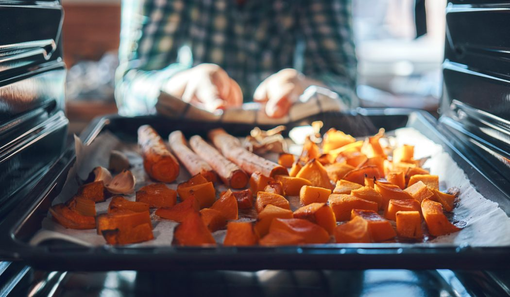 Someone is pulling a pan of roasted carrots, squash and sweet potato out of the oven.