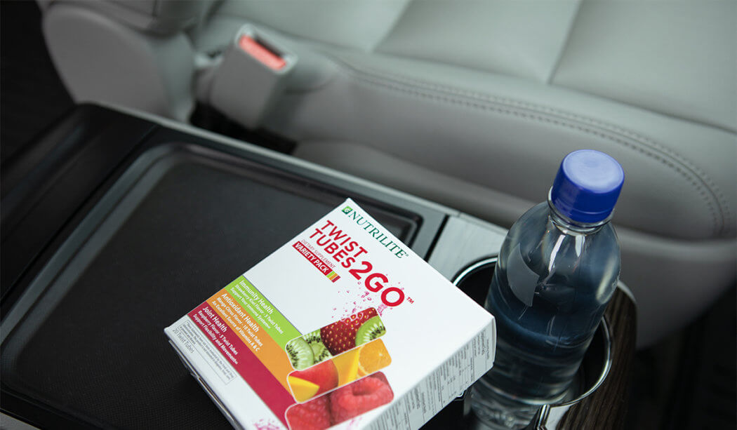 A package of Nutrilite Twist Tubes 2GO sits near a bottle of water in a car console.