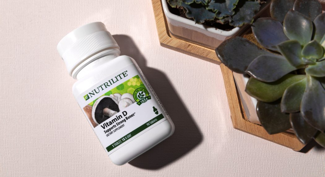 A bottle of Nutrilite Vitamin B lies next to some succulents.