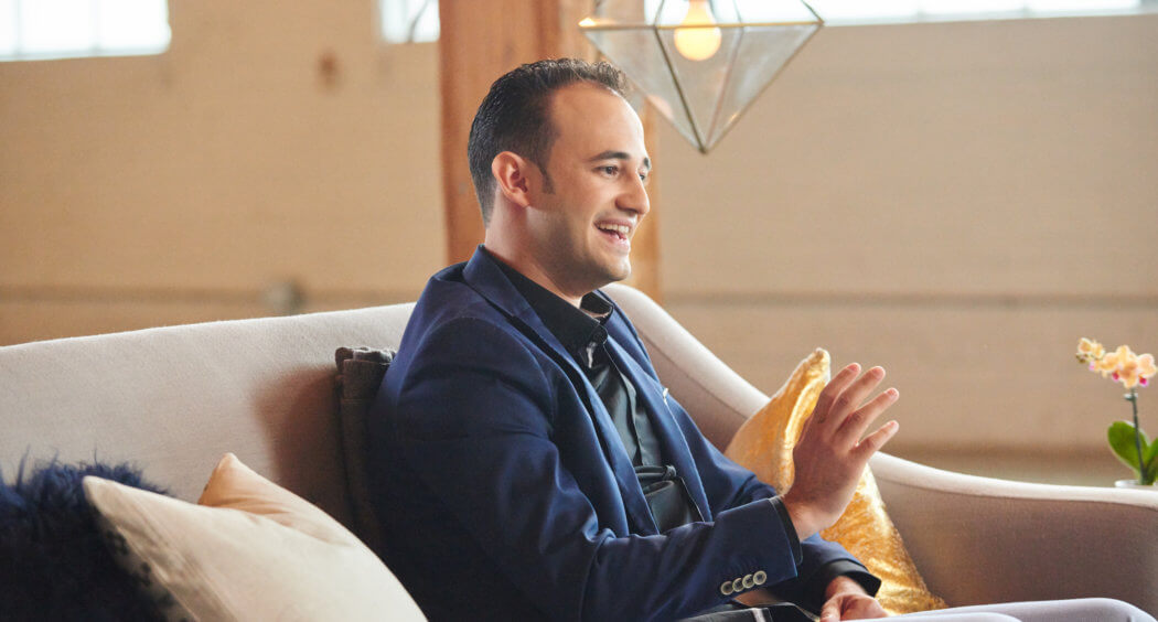 Amway IBO Omar Fabel sits on a couch gesturing with his hands and smiling while he talks.