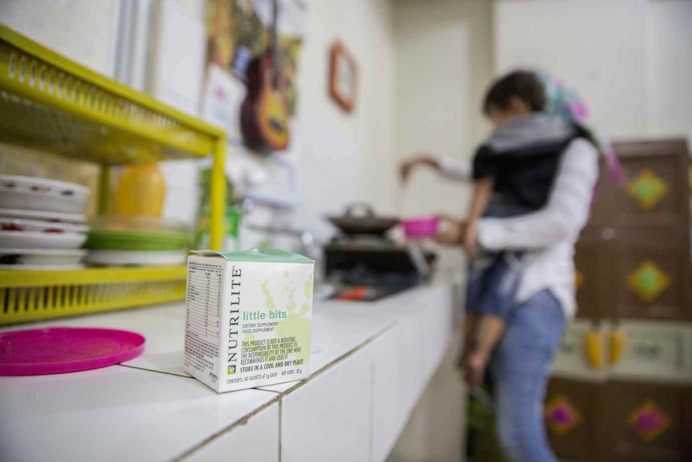 A mom holds her child in her kitchen in the background, preparing a meal with Nutrilite Little Bits. A box of Nutrilite Little Bits sits on the counter in the foreground.