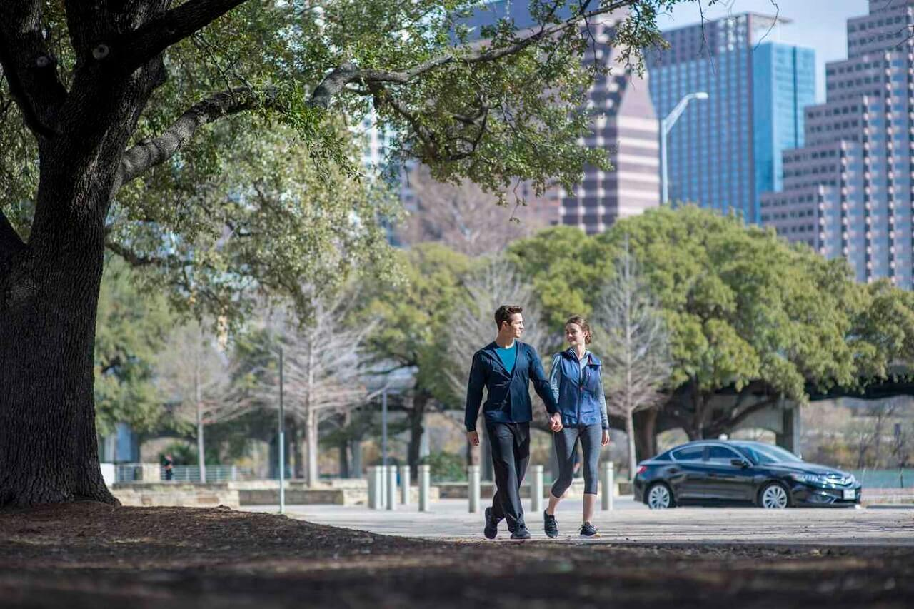 A man and woman walk hand in hand in a city park with the skyline behind them.