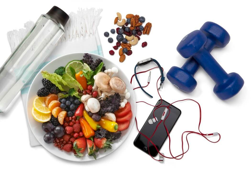 Diet and exercise display showing healthy food, water bottle, hand weights, fitess tracker and phone with earbuds.