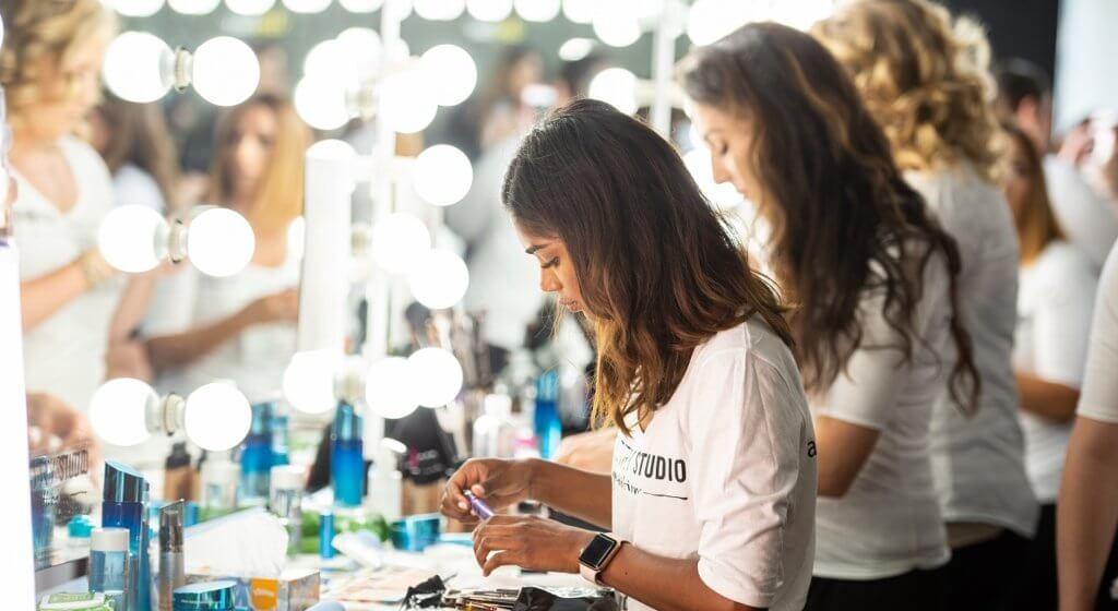 Three Artistry passionistas stand at a lighted mirror table backstage at New York Fashion Week preparing their products for application.