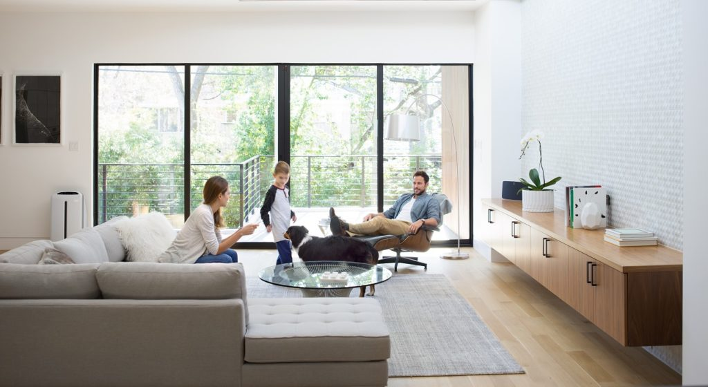 A family sits in their bright, airy living room with their dog and an Atmosphere Sky in the background.