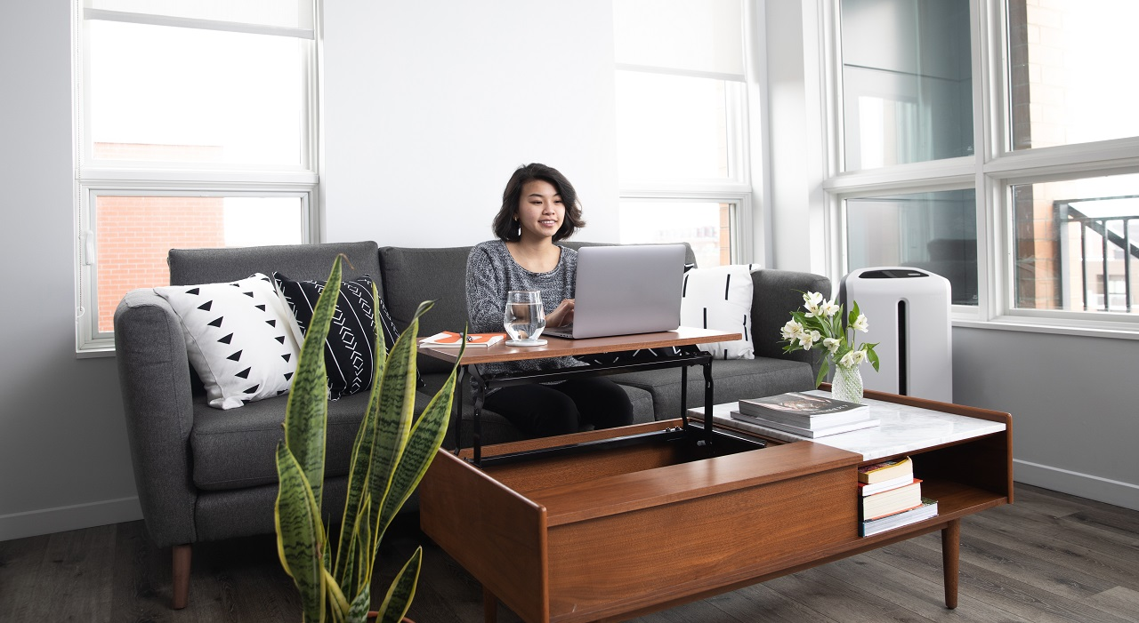 Woman sitting on couch with laptop in her apartment.