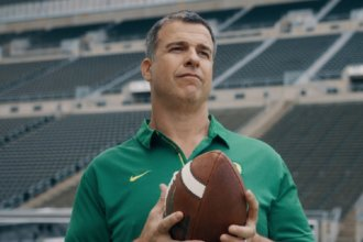 University of Oregon Head Football Coach Mario Cristobal holds a football while standing in an empty stadium. He provided Amway Connections with Inspired Coaching advice.