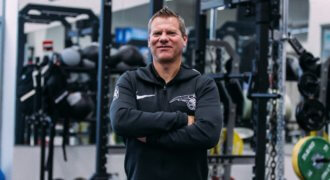 Orlando Magic High Performance Director David Tenney stands in front of workout equipment with his arms folded and smiles at the camera.