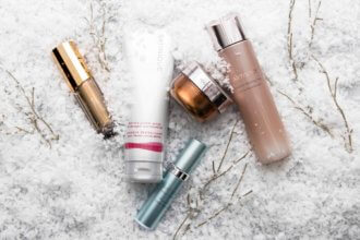 Packages of Artistry skincare products ideal for winter weather laying on heavy snow with twigs.