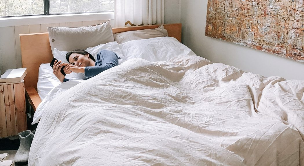 A woman lies in bed while looking at her phone.