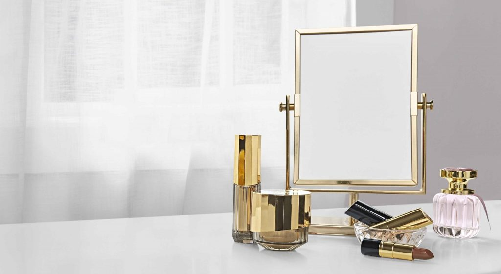 A bottle of Artistry Flora Chic perfume and other Artistry cosmetics and skincare products sit on a dresser top next to a mirror with an window in the background.
