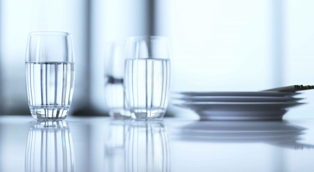 Three glasses of crystal clear water sit on a table next to a stack of plates.