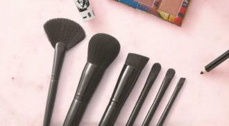 A set of the six new Artistry makeup brushes lie on a pink background. Artistry eye shadow, mascara and eyeliner can be seen at the edges of the frame.