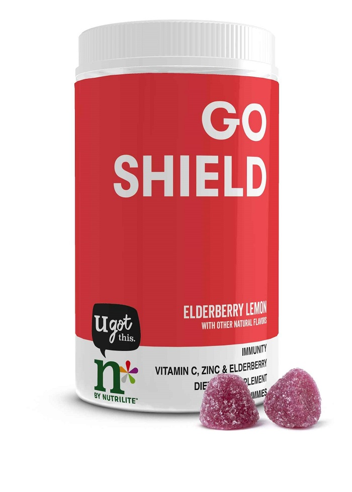 A canister of n* by Nutrilite Go Shield gummies with two gummies sitting on the counter next to it.