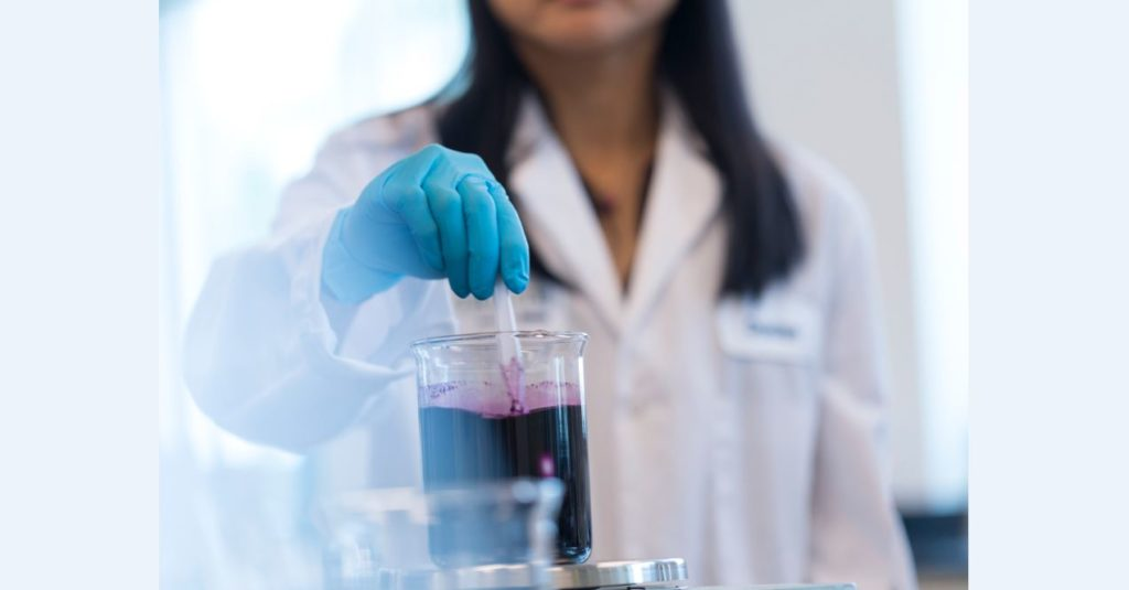 A female Nutrilite scientist is shown working in a lab with a beaker filled with a purple liquid.