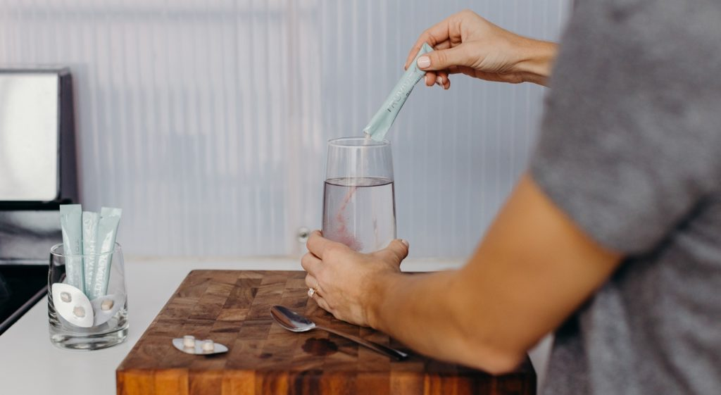 A woman mixes a TruAqua Powder Drink. in a clear glass on a cutting board. TruAqua Dietary Supplement tablets lie nearby.
