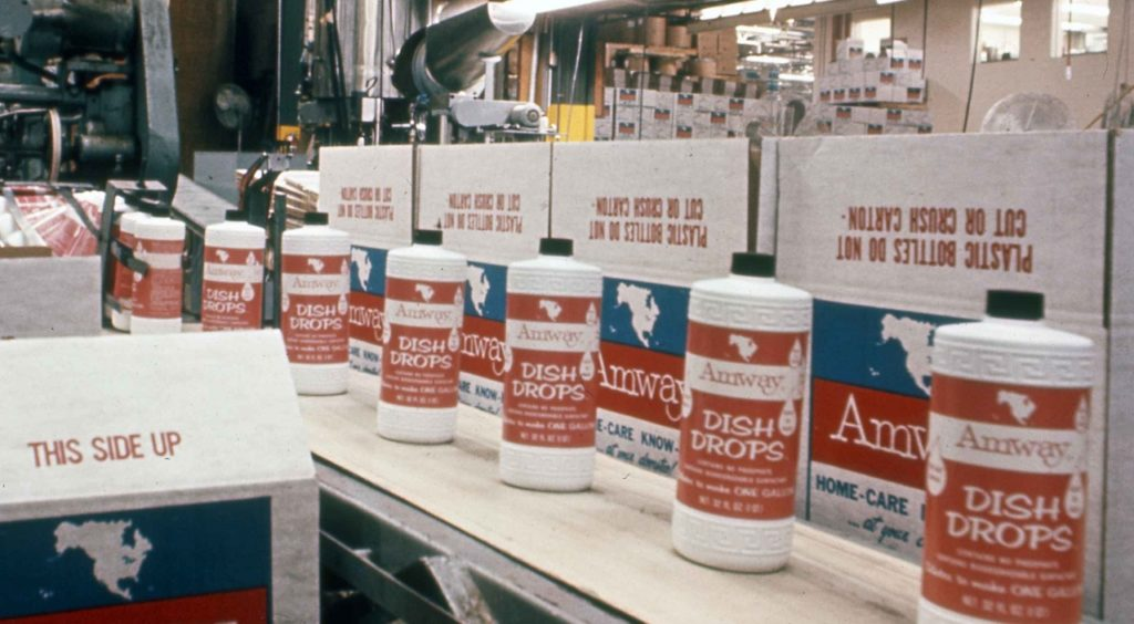 Early packages of Amway Dish Drops dishwashing liquid shown on the production line. It was one of Amway's first products and remains popular today.