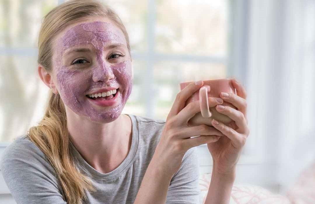 A woman with a ponytail wears an Artistry Signature Select Mask while holding a cup of coffee or tea.
