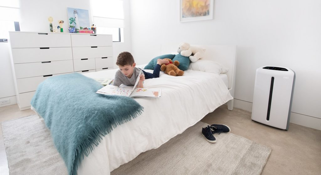 A young boy reads on his bed.