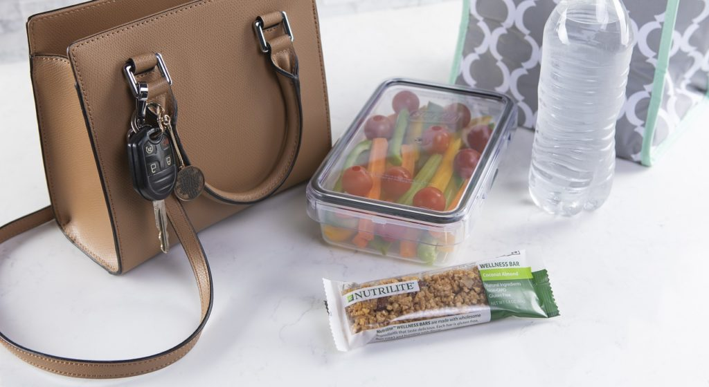 A Nutrilite Wellness bar lies next to a plastic container of vegetables, a purse, a bottle of water and a lunch bag.
