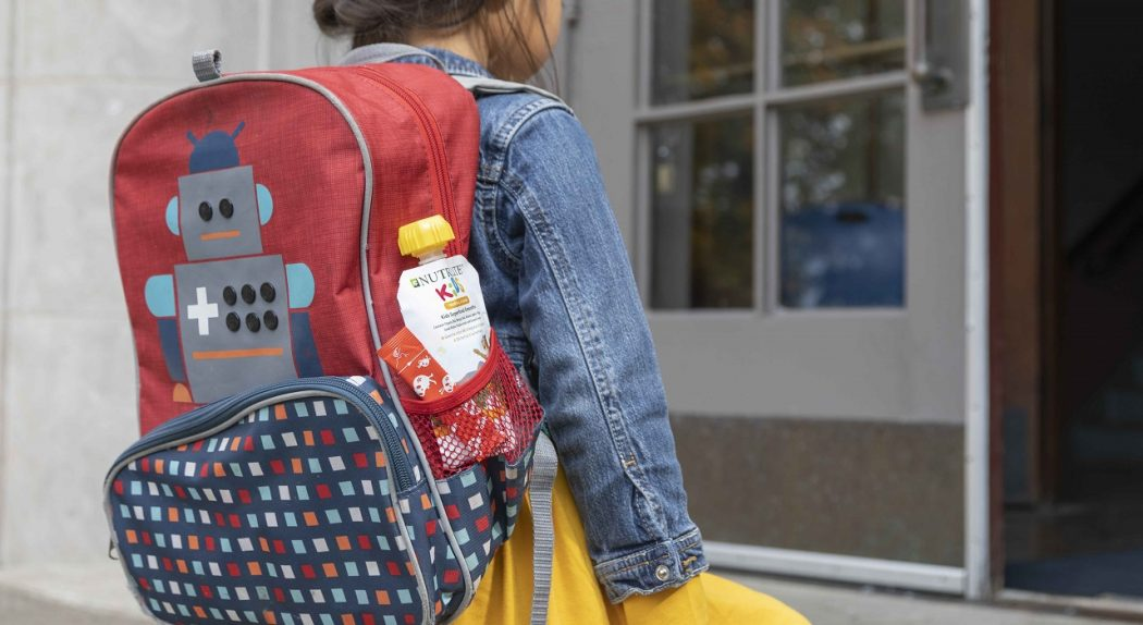 A little girl climbs the steps into her school. A Nutrilite Kids Superfood Smoothie can be seen peeking out of a backpack side pocket.