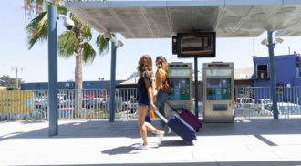 Two women walk along a bus station terminal toting rolling suitcases. Palm trees are in the background.