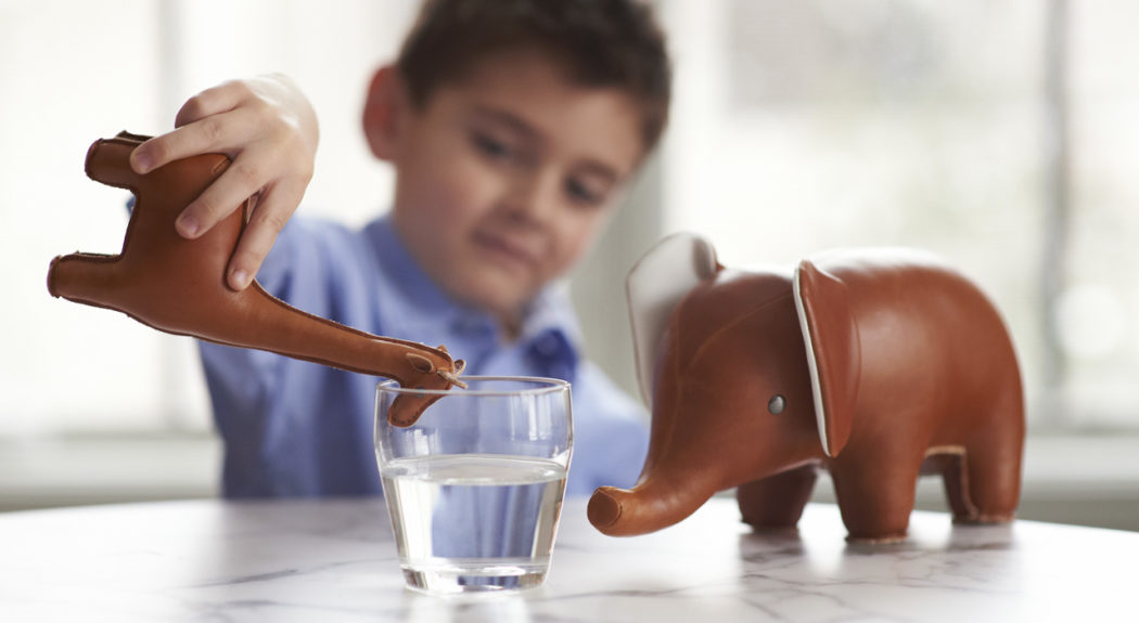 A small boy pretends to have his toy giraffe drink out of a glass of tap water. A toy elephant sits nearby.