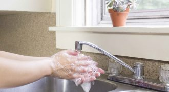 Hands are shown lathered up with soap under running water at a kitchen sink.