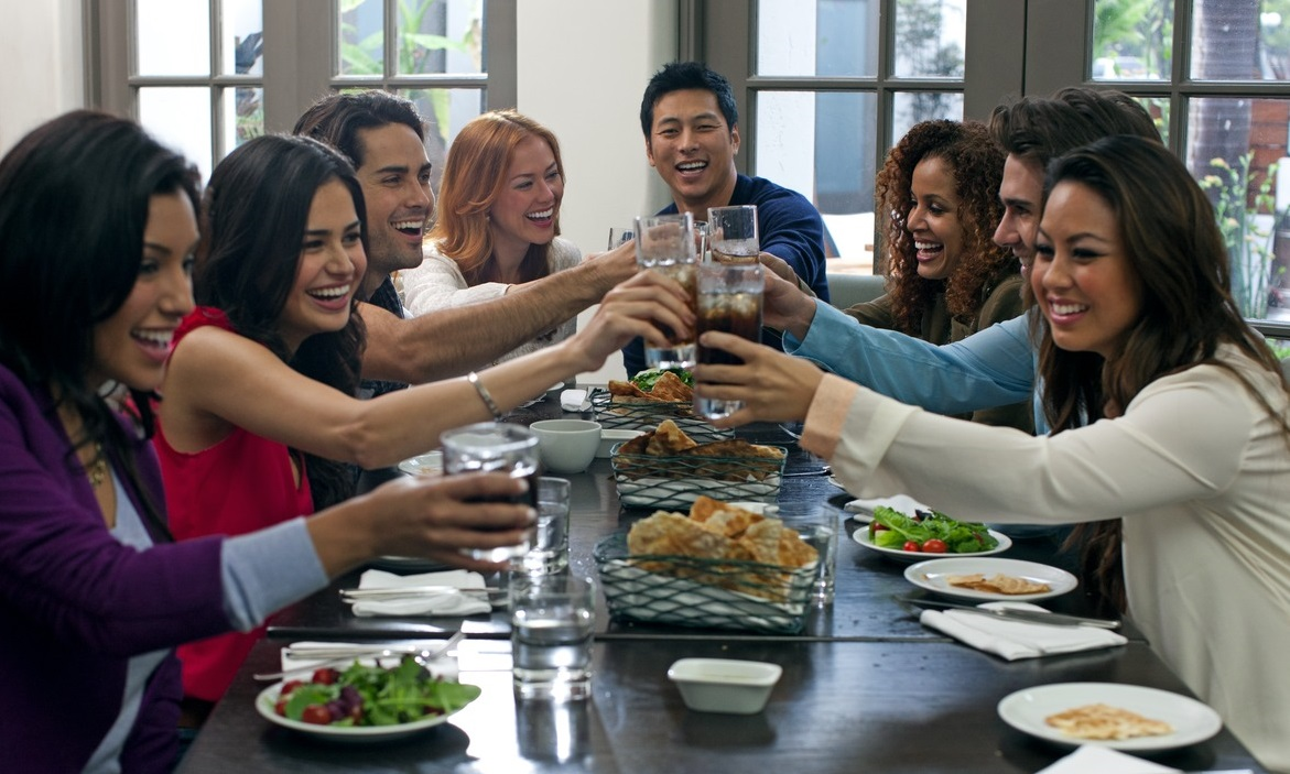 Guests sitting down at a dinner party raise their glasses in a toast.