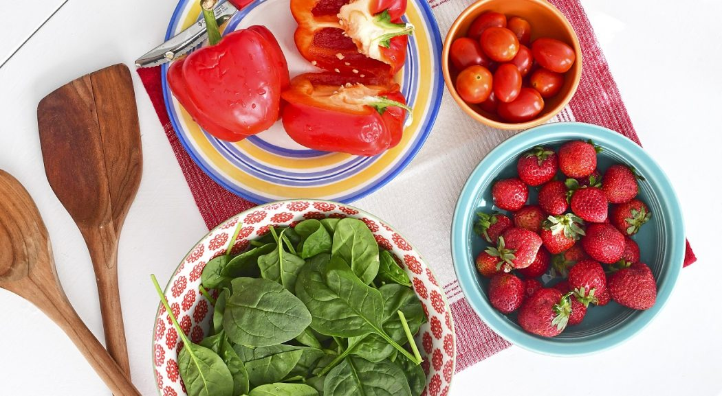 An overhead view of bowls of spinach, strawberries, red peppers and cherry tomatoes.