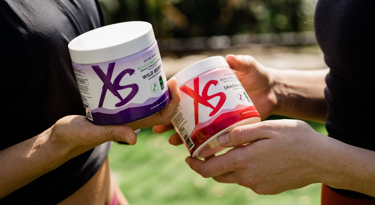 A closeup view of two people's hands. Each is holding a container of XS Muscle Multiplier Essential Amino Acid Supplement.