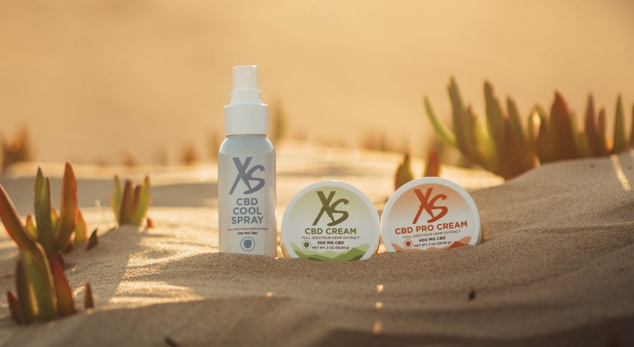 A bottle of XS CBD Cool Spray and containers of XS CBD Cream and XS CBC Pro Cream sit side by side in the sand on a beach.