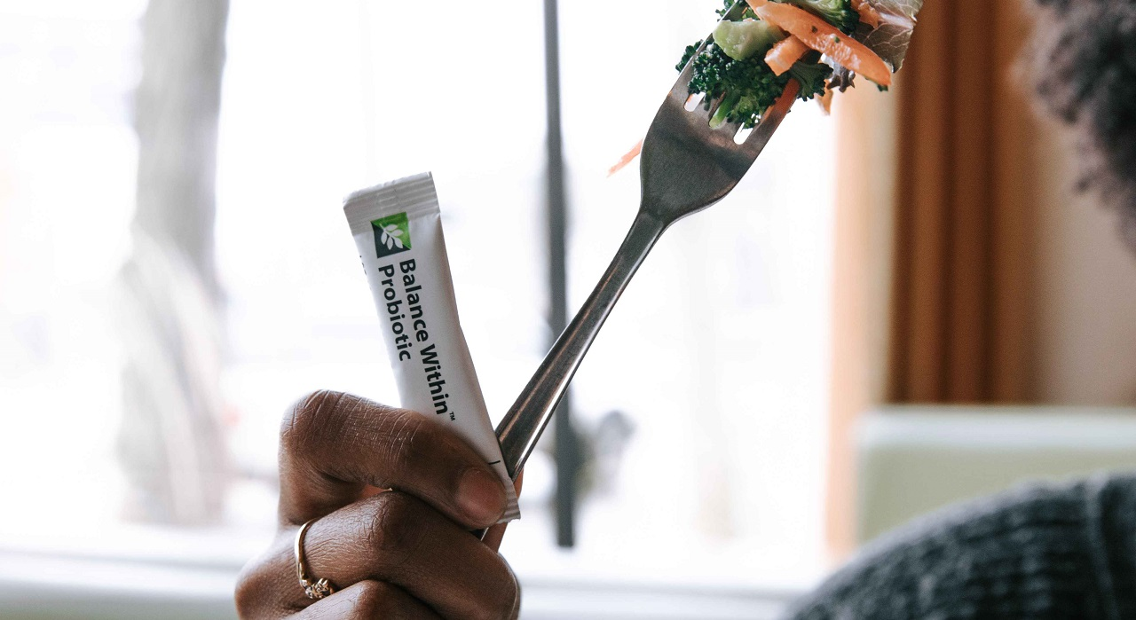 A person holds up a forkful of salad while also holding a small packet of Nutrilite Balance Within Probiotics.