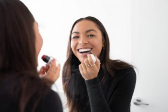 A woman smiles at the camera through her reflection in a mirror as she applies Artistry Studio Cheek and Lip Duo.