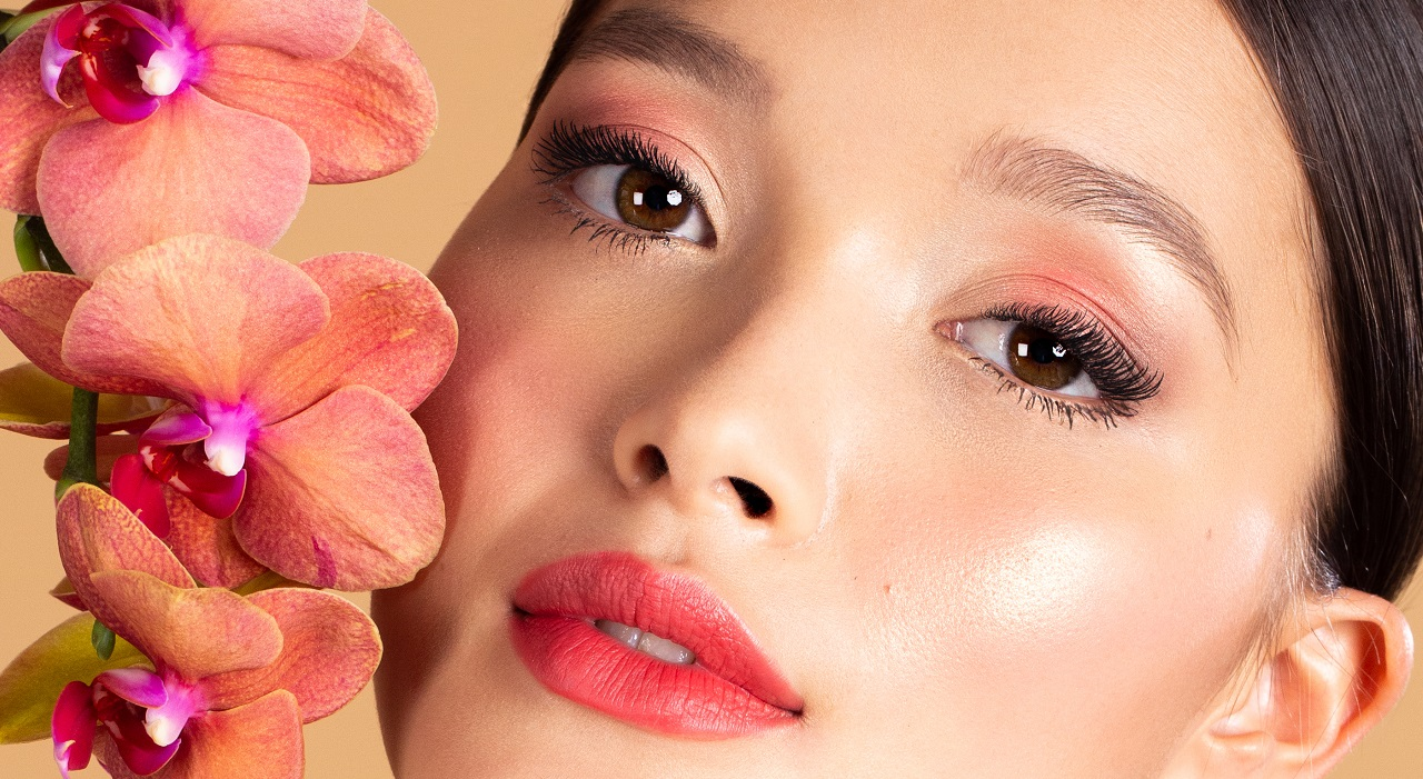A woman wearing beautiful Artistry makeup holds flowers near her face. Her eyes are almond shaped.