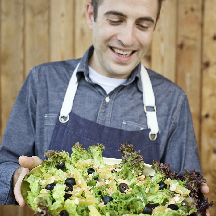 A man wearing an apron smiles down on the large Greek salad he is holding