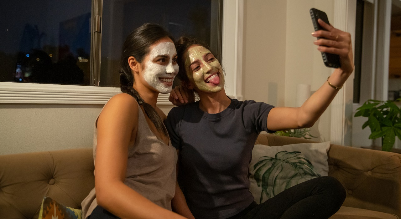 Best friends take a selfie while using an Artistry mask and sitting on a couch.