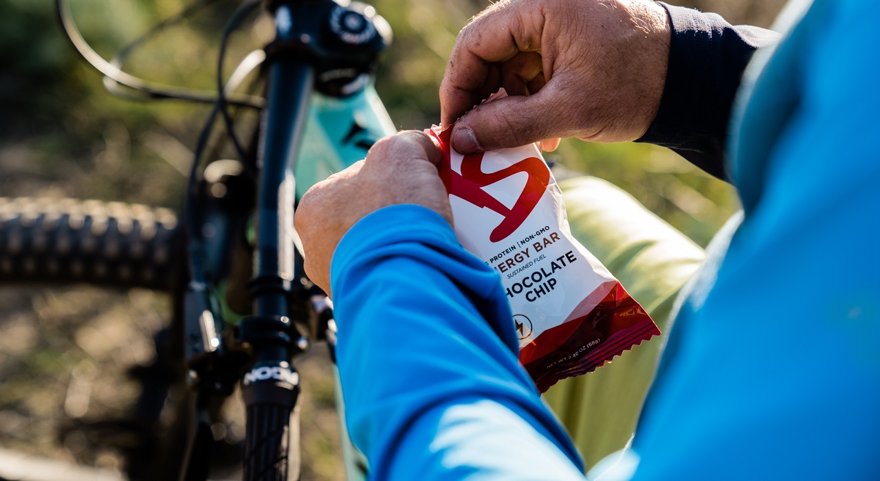 The hands of a person on a bike are shown opening an XS Energy Bar.