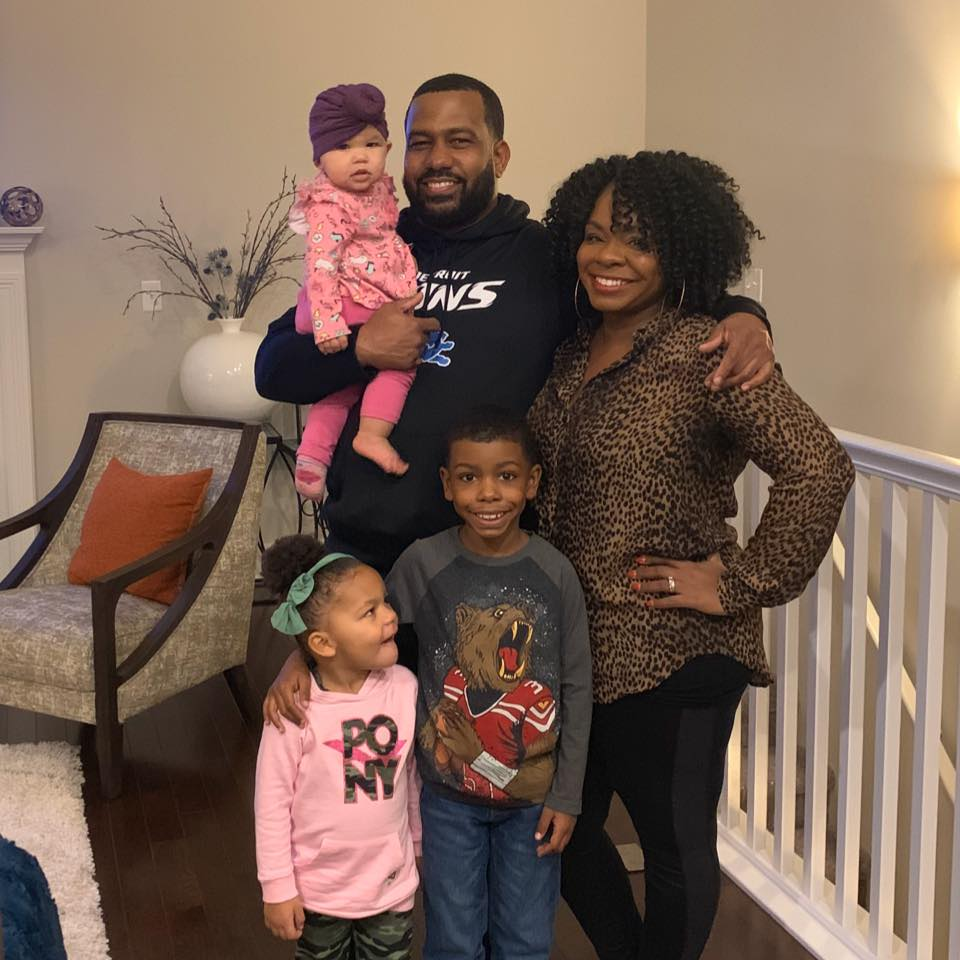 The Trice family poses for a photo in their home. Robert stands in the back holding Olivia, in front from left to right are A'Rayah, Caleb and Latricia.