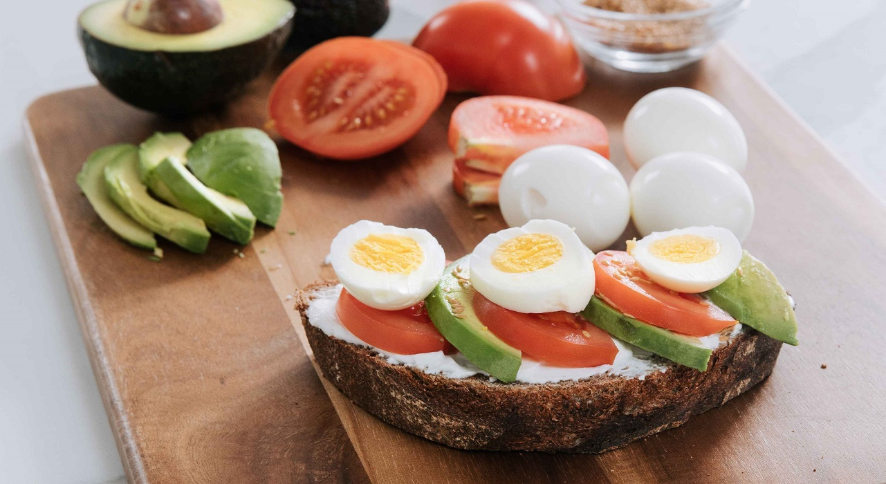 A piece of whole grain toast topped with cream cheeses, tomatoes, avocados and hard-boiled eggs sits on a wooden cutting board surrounded by the ingredients.