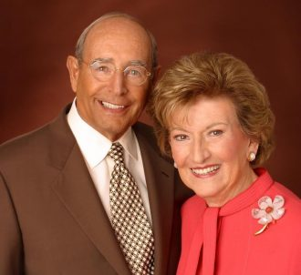 A portrait of Richard and Helen DeVos. He is dressed in a brown suit and she is in a coral outfit with a flower pin.