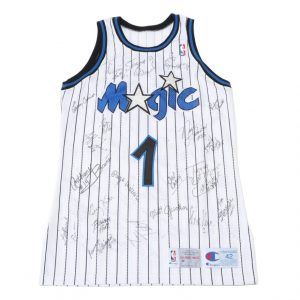 An Orlando Magic jersey with the number 1 on one side and DeVos on the other. It is signed by multiple players, including Shaquille O'Neal.