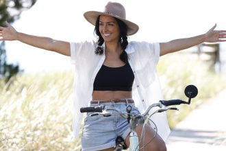 A smiling woman sits on a bike on a sunny day stretching her arms out wide in enjoyment.